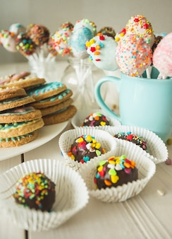 Photo of colorful cake pops and cookies with icing