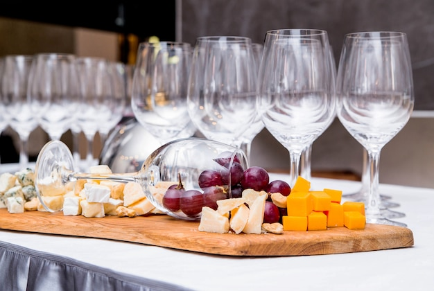 Photo of a composition from a wine glass and cheese on a buffet table