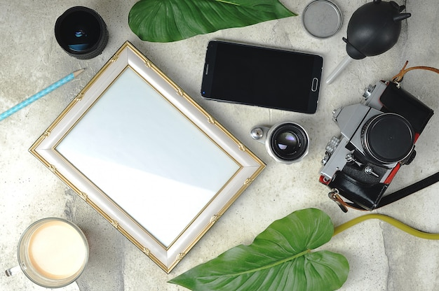 Photo composition-an old film camera, lenses, an empty photo frame and a cup of coffee