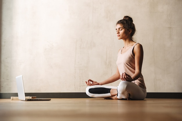 Photo of concentrated attractive woman in sportswear meditating with zen fingers and using laptop while sitting on floor at home