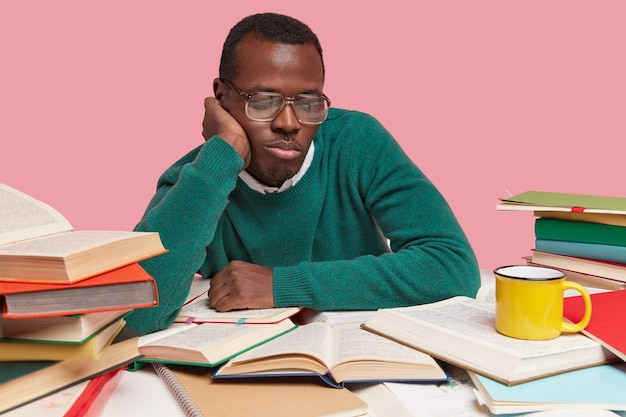 Photo of concentrated black man focused down in opened books, involved in reading, wears green jumper, finds out new information