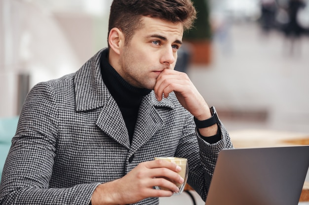 Photo of concentrated businesslike man working with silver laptop in cafe outside, drinking coffee in glass