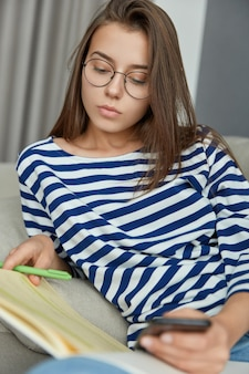 Photo of concentrated female reader reads book, underlines information with pen, tries to enrich her vocabulary, holds modern mobile phone, wears optical glasses for good vision, has serious look