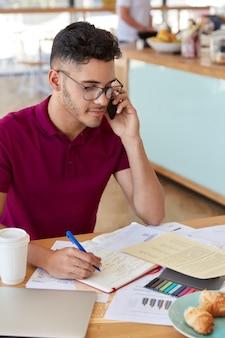 Foto di un lavoratore maschio concentrato impegnato con scartoffie, tiene la penna, ha un taglio di capelli alla moda, vestito con una maglietta casual, comunica tramite cellulare, gode di gustosi croissant con caffè. lavora in mensa