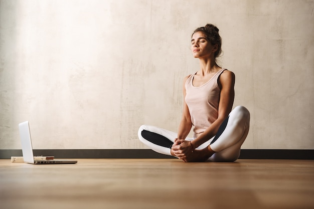 Photo of concentrated nice woman in sportswear doing exercises with closed eyes and using laptop while sitting on floor at home