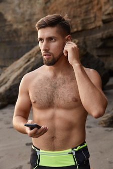 Photo of concentrated ushaven young european man likes gymnastics, uses cell phone and earphones for listening audio tracks