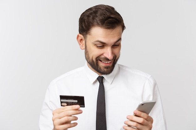 Photo of confident entrepreneur man in suit and tie holding smartphone and credit card for paying online