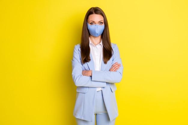 사진 자신감 있는 임원 회사 소유주는 손을 교차할 준비가 되어 있는 원격 covid 검역소에서 파란색 블레이저 재킷 바지 바지 의료 마스크 격리된 밝은 광택 색상 배경을 착용합니다.