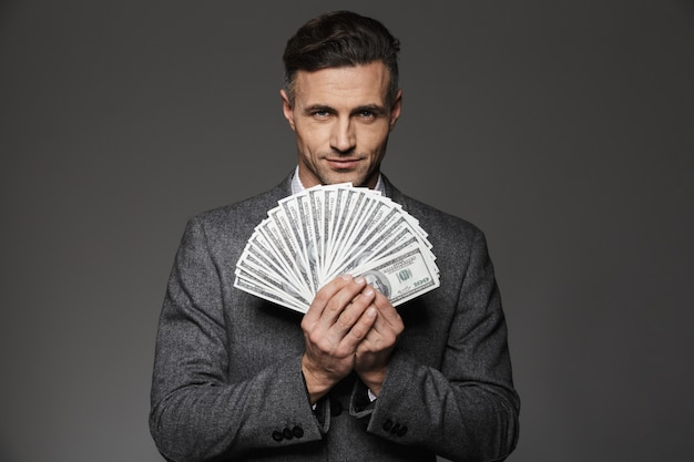 Photo of confident guy 30s in business suit holding fan of money dollar bills and , isolated over gray wall