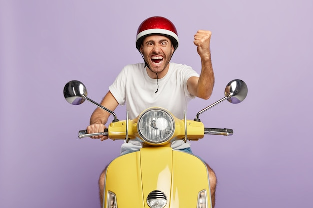 Photo of confident guy with helmet driving yellow scooter