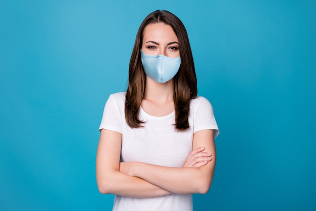 Photo of confident lady arms hands crossed bossy worker intelligent person successful career team member wear casual medical mask white t-shirt isolated blue color background