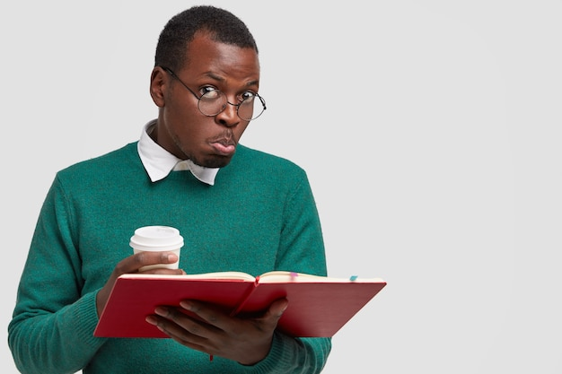 Photo of confused black man purses lips, has puzzled facial expression, reads necessary information for exam
