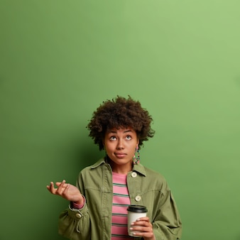 Photo of confused hesitant young woman raises palm in bewilderment and concentrated above, drinks takeaway coffee, stands indoor, wears fashion clothes, isolated on green wall, copy space