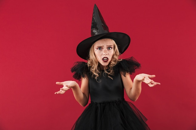 Photo of confused little girl witch in carnival halloween costume