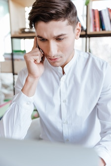 Photo of confused man dressed in white shirt using laptop computer while talking by phone. coworking. look aside.