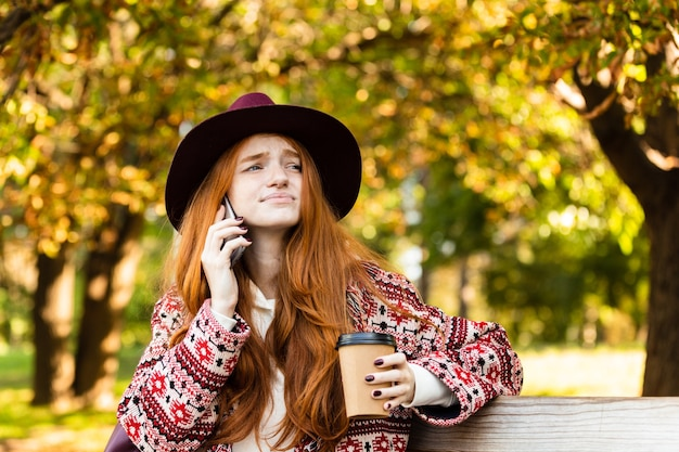 Photo of a confused sad young student redhead girl in autumn park talking by mobile phone drinking coffee.