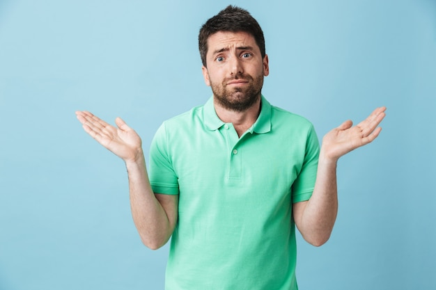 Photo of a confused young handsome bearded man posing isolated over blue wall.