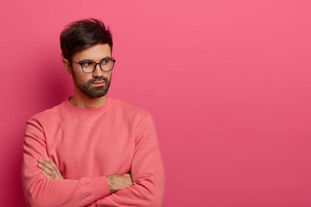 Photo of contemplative unshaven man in glasses keeps hands crossed over chest, thinks over preparing something interesting for project, ponders on how to solve situation, dressed in rosy sweater