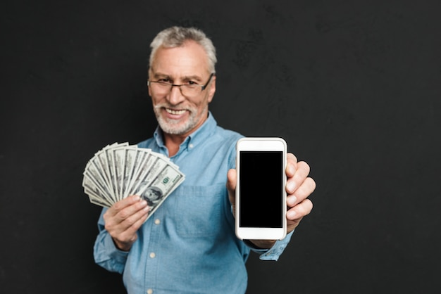 Photo of content retired man 60s with gray hair holding fan of money dollar cash and demonstrating cell phone, isolated over black wall