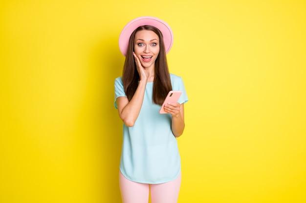 写真クレイジー驚いた女の子のブログ使用スマートフォン感動ソーシャルメディアニュースタッチハンドフェイスウェアブルーピンクサンハットパンツズボン孤立した明るい輝き色の背景