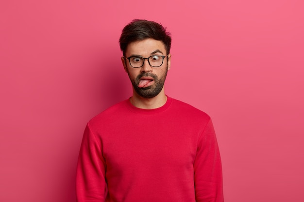 Photo of crazy bearded man sticks out tongue, crosses eyes, feels tired and bored, wears glasses and red sweater, foolishes around, poses against pink wall. comic face expressions concept