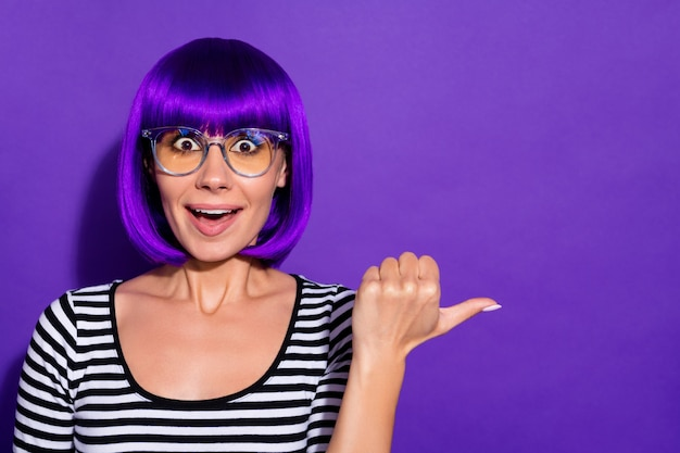 Photo of crazy lady indicating finger empty space with open mouth wear wig striped pullover isolated purple background