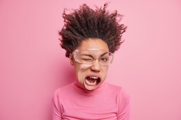 La foto di una donna etnica pazza e pazza dalla pelle scura che strizza l'occhio tiene la bocca aperta ha i capelli ricci sollevati esclama chiassosi vestita casualmente