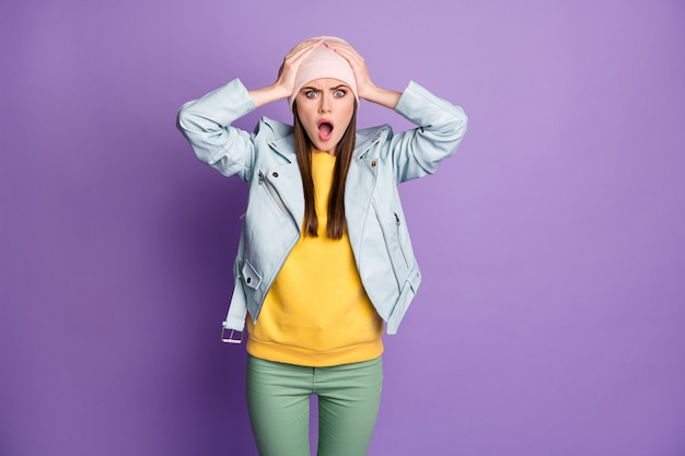 Photo of crazy shocked attractive lady teenager hold arms on head open mouth listen awful quarantine news wear casual hat blue modern jacket pants isolated purple color background