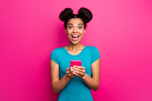 Photo of crazy youngster dark skin lady hold telephone open mouth cheerful mood
