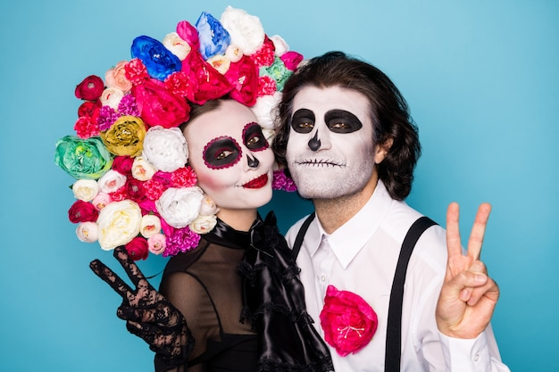 Photo of creepy creature couple man lady cuddle show v-sign greeting demon fellows religious ritual wear black dress death costume roses headband suspenders isolated blue color background
