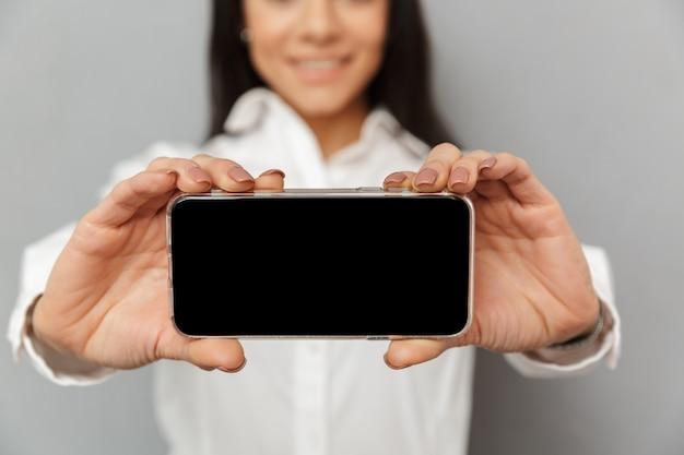 携帯電話を手で押し、灰色の背景に分離されたカメラでcopyspaceの黒い画面を示す事務服でブルネットの女性30代の写真をトリミング