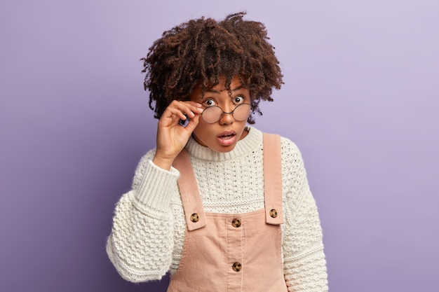 Photo of curious dark skinned lady looks surprisingly curiously through round glasses, can not believe in shocking news, wears oversized white jumper and overalls, stands over purple wall
