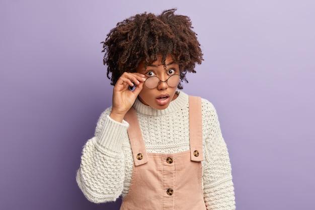 La foto di una donna curiosa dalla pelle scura sembra sorprendentemente curiosamente attraverso occhiali rotondi, non riesce a credere a notizie scioccanti, indossa un maglione bianco e una tuta oversize, si trova sopra il muro viola