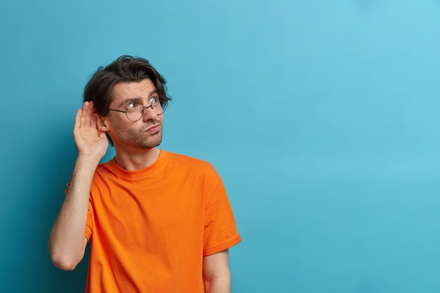La foto di un uomo curioso tiene la mano vicino all'orecchio e ascolta le informazioni private, cerca di sentire i pettegolezzi, ha un'espressione incuriosita, indossa occhiali rotondi e maglietta arancione, copia spazio sul muro blu