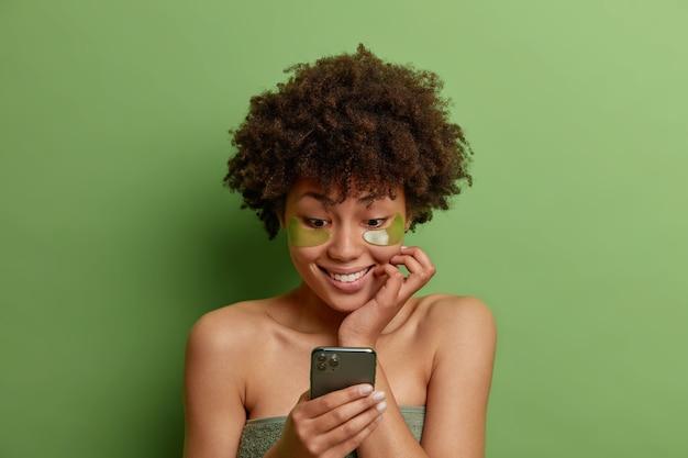 La foto della donna soddisfatta dai capelli riccia applica le toppe idratanti verdi sotto gli occhi si sottopone a trattamenti di bellezza