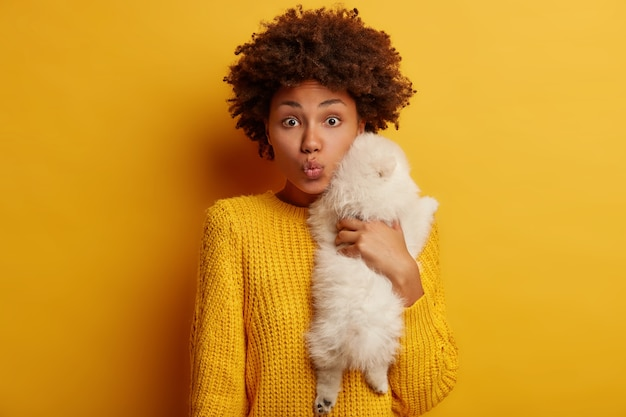 Photo of curly lady carries small white puppy, embraces dog with love, expresses care, prepare for groomer visit, dressed in yellow jumper, stands indoor.
