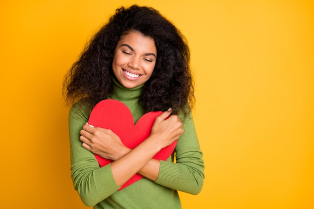 Photo of curly wavy satisfied pleased cheerful girl at leisure embracing gifted heart smiling toothily in green sweater isolated vibrant color background