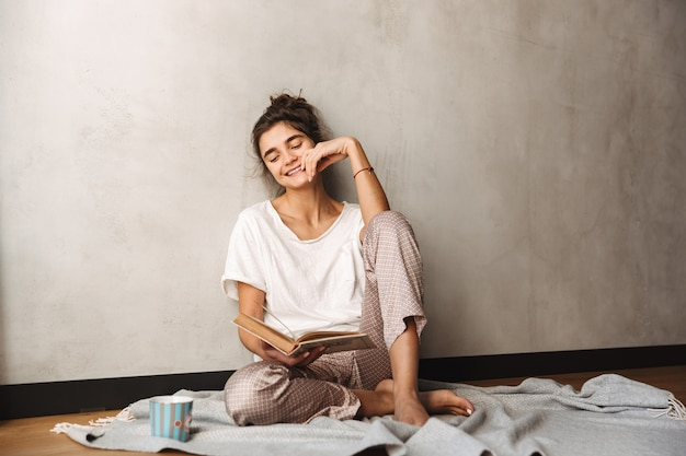 Photo of cute amazed woman wearing leisure clothes drinking coffee and reading book while sitting on floor at home