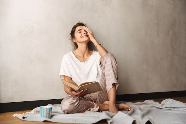 Photo of cute amazed woman wearing leisure clothes with closed eyes drinking coffee and reading book while sitting on floor at home