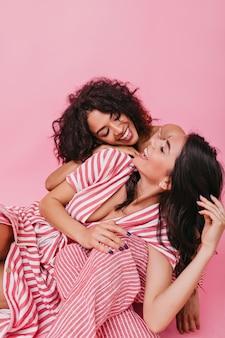 Foto di ragazze attraenti carine con i capelli scuri, vestite in pigiama a righe luminose, divertendosi