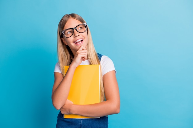 Photo of cute cheerful pupil girl thinking looking empty space wear spectacles hold book isolated on pastel blue color background