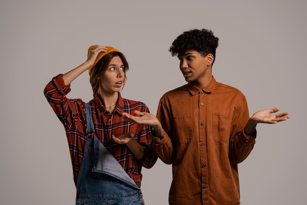 Photo of cute couple farmers look worried about something. white woman wears denim overall, black man shirt isolated brown color background.