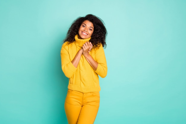Photo of cute dark skin wavy lady holding hands together overjoyed spring mood wear yellow knitted pullover stylish pants isolated blue teal color wall