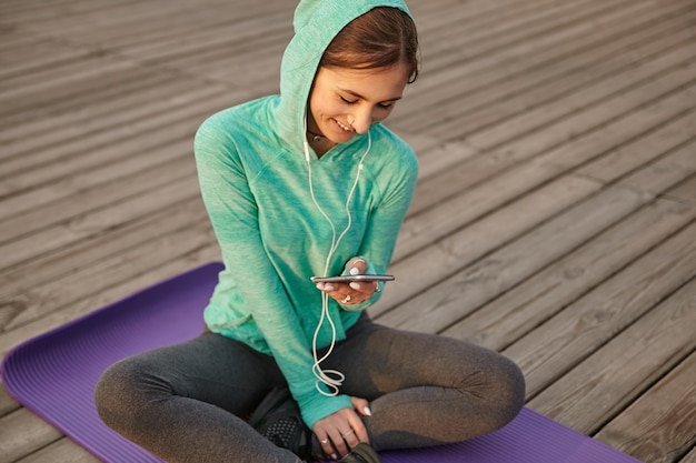 Photo of cute girl in bright sportswear, listening cool playlist on headphones after morning yoga and enjoy the sun, chatting with friends and looks at the display if smartphones.
