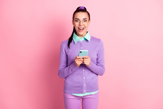 Photo of cute girl hold telephone open mouth excited wear specs purple cardigan isolated pink color background