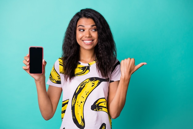 Photo of cute girl hold telephone screen empty space direct thumb look side wear banana print t-shirt isolated turquoise color background
