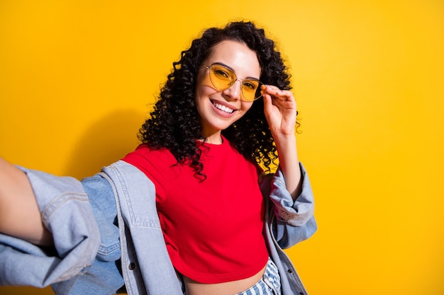 Photo of cute girl make shoot selfie toothy smile wear red t-shirt jacket sunglass isolated yellow color background
