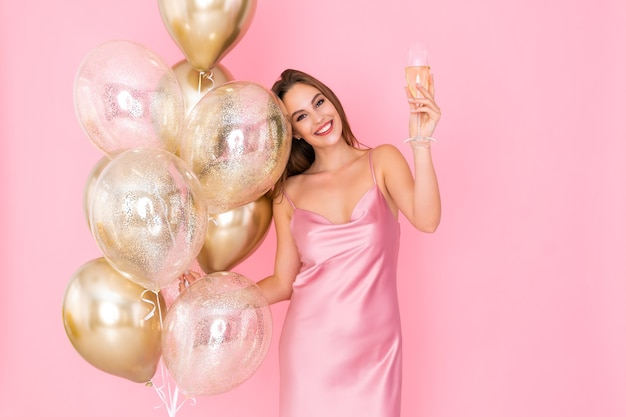 Photo of cute girl raises up glass of champagne holds many air balloons came to party celebration