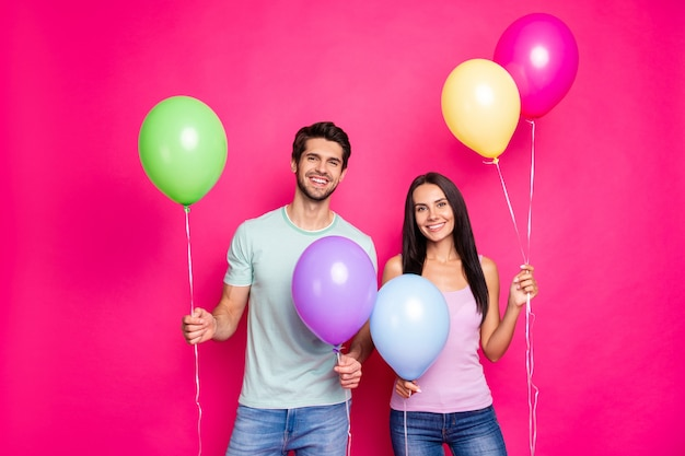 Photo of cute guy and lady holding air balloons in hands came to first summer time party ready chill wear casual outfit isolated pink color background