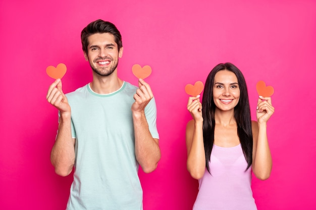 Photo of cute guy and lady holding little paper hearts in hands expressing positive comments on new social network post wear casual outfit isolated pink color background